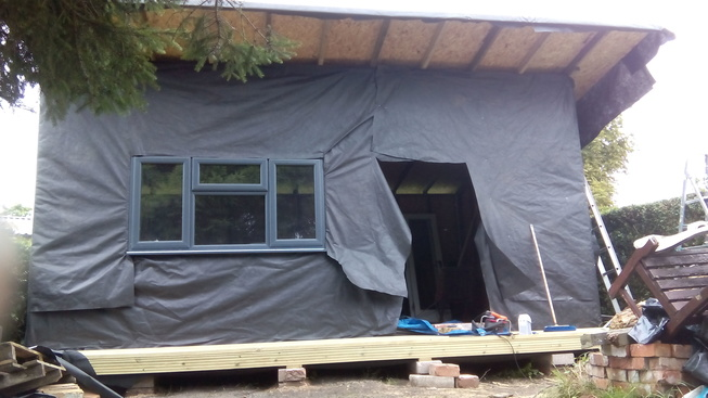 Window and doors in, finally, membrane tacked on